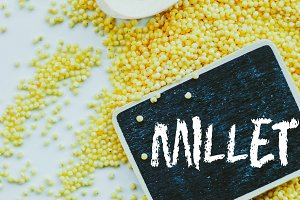 """organic millet seeds and chalkboard with word """"millet"""" on white background"""
