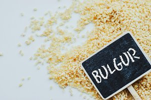 "Organic bulgur raw wheat grain and chalkboard with word ""bulgur"" on white background"