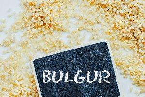 "Organic bulgur raw wheat grain and chalkboard with word ""bulgur"" on white background"