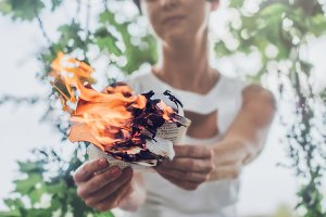Woman writer holds book pages with flame in the hands. Concept - woman says goodbye to past memories and burning her diary