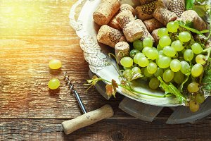 Grapes, corks and corkscrew on a wooden old table, rustic style