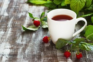 Tea with raspberries and raspberries on a wooden background. Place under the text