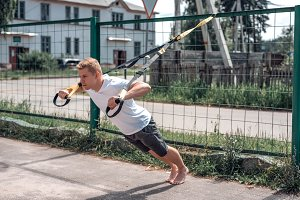 A sports person, in the fresh air is engaged in training trx, in sports clothes, in the summer city, wringing out. Strength and stamina motivation.