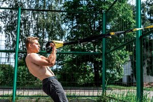 Male athlete, trains in fresh air, summer trx training, Balance motivation, tanned skin in shorts.