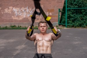 Male athlete close-up, trains nature in city, summer trx training, Feel your strength and balance, motivation, tanned skin shorts. Exercise pectoral muscles. A sunny day.