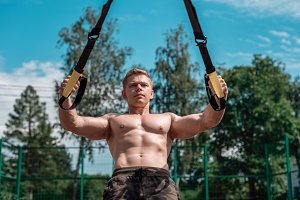 Male athlete is an excellent trx training, fresh air nature in summer, feel your strength and balance, motivation, tanned skin. Exercise of muscle of the chest. A sunny day. Stamina of a man. Against the blue sky.
