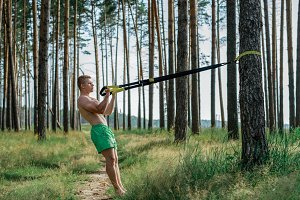 Male athlete excellent training trx, fresh air in nature summer in park, feel your strength, motivation, full-length. Exercise of the biceps muscles. A sunny day. Stamina of a man. Against the background of trees.
