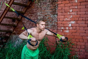 Male athlete excellent training trx, fresh air nature in summer in city, feel your strength, motivation, close-up. Exercise of muscle is the chest push-up. In evening at wall. Stamina of a man. Against background of the stairs.