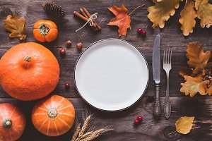 Autumn thanksgiving table setting with empty plate, cutlery and pumpkins