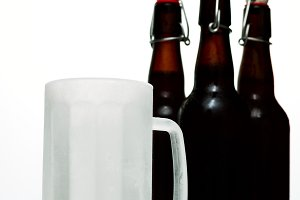 Beer glass with dark beer and two full beer bottles on a white background