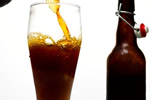 Dark beer is pouring from a bottle into a misted beer glass on a white background