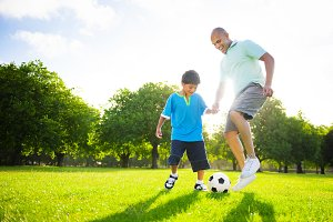 Boy playing soccer with his father
