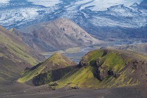 Icelandic landscape with green mountains and glacier