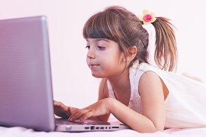Little girl playing with laptop