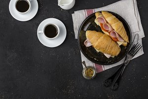 Fresh croissant sandwich with ham, cheese and tomatoes