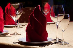 Table in a restaurant with a yellow tablecloth, red napkins, wine glasses and cutlery.