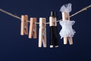 Bride and groom clothespin toys, clothesline. Abstract woman in white dress man character with black suit hat. Love concept photo.