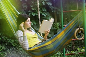 serene scene with teen girl in hammock with apricot reading book