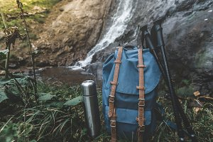 Hipster Blue Backpack, Trekking Poles And Thermos Closeup. View From Front Tourist Traveler Bag On Waterfall Background