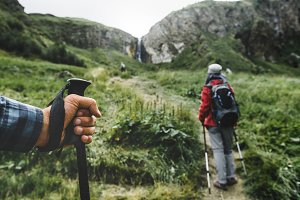 A group of travelers with rucksacks and trekking sticks rises uphill