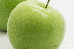 Green apple on white wooden table, d