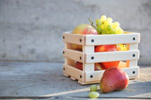 Grapes, pear and apple fruits in a box