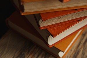 Autumn cozy still life. Pile of orange books on wooden table. Fall reading list.