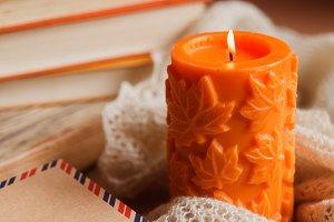 Autumn cozy still life of big orange candle, pile of books and vintage kraft envelopes.