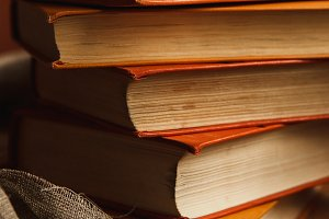 A stack of paper books in orange color on textured wooden surface. Autumn mood concept. Time to read.