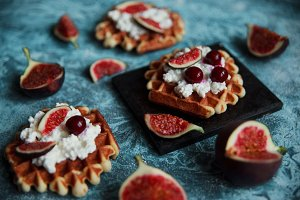 Still life of belgian biscuit waffles with cottage cheese, fresh figs and cherry. Healthy vegetarian breakfast.