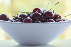 Cherries in white bowl, fruit on out