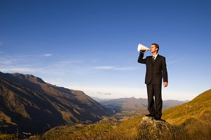 Businessman shouting on the mountain