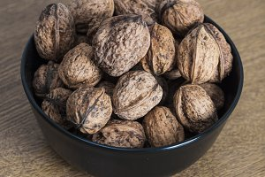 Walnuts in a bowl on wooden table