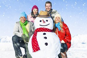 Group of friends posing with snowman