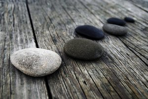 Smooth pebbles on an old wooden pier