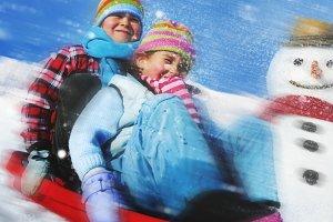 Siblings playing snow sledge