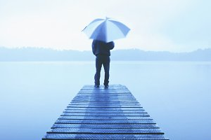 Man holding an umbrella on a jetty