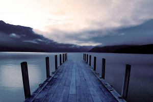 Boat jetty and calm lake at sunrise