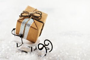 Small gift box on white sledge. Merry Christmas greeting card