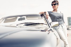 Senior Woman Standing Next To Convertible Classic Car