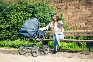 Young Mother With Baby Stroller In The Park