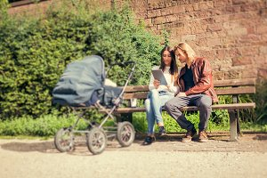 Young Parents With Baby Stroller In The Park