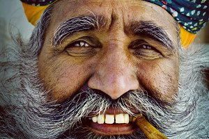 Bearded Indian man smoking a pipe