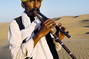 Indian man playing wind pipe