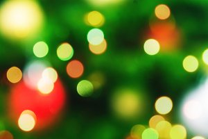 Festive bright bokeh lights on blurred fir tree background