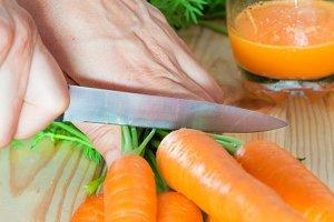 Female hands cutting carrots