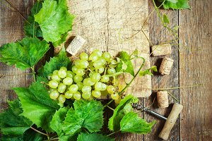 Grapes,a bottle of wine, corks and corkscrew on a wooden old table, rustic style