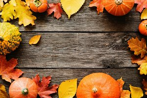 Autumn seasonal background with fallen leaves and pumpkins