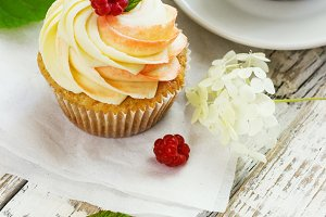 Delicate vanilla cupcakes with cream and raspberries on a white wooden background with a cup of coffee