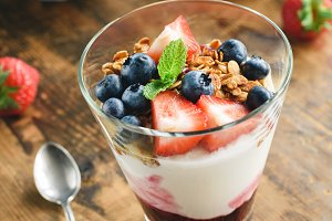 Natural yogurt with granola, blueberries and strawberries
